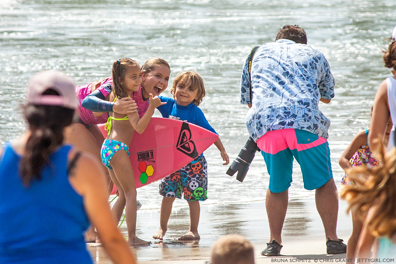 Bruna Schmitz shares a moment with two surf-stoked kids at the 2013 Supergirl Pro in Oceanside, California. Surf photo by Chris Grant, Jettygirl Online Surf Magazine.