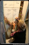 Keala Kennelly signing the Women On Waves exhibit board. Photo courtesy of the California Surf Museum.