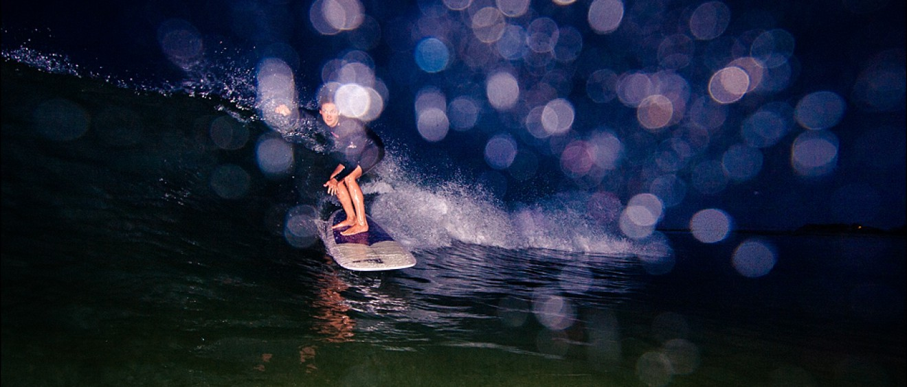 Julie Cox surfing at night at First Point Malibu. Surf photo by Chris Grant.