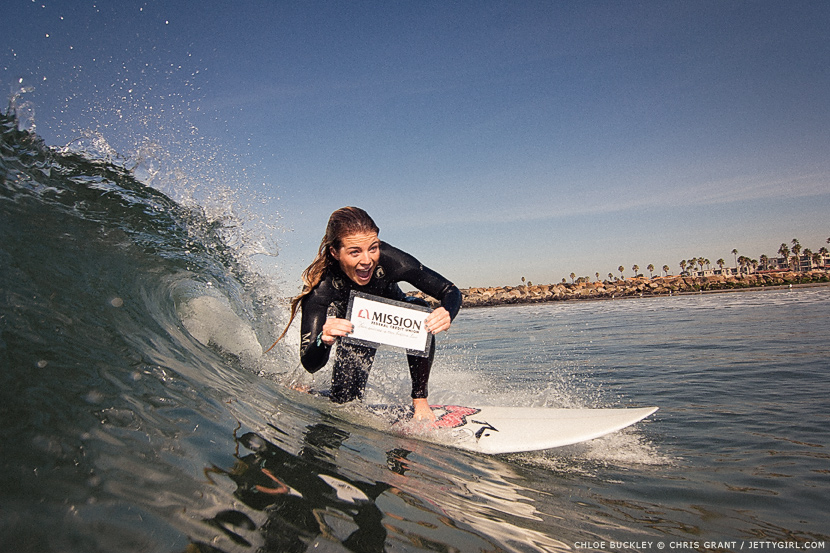 Chloe Buckley surfing the largest wave on the tiniest of days while holding a Mission Fed sign. Surf photo by Chris Grant, Jettygirl Online Surf Magazine.