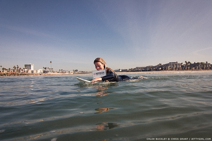 Chloe Buckley paddles into the lineup with a Mission Federal sign between her teeth. Surf photo by Chris Grant, Jettygirl Online Surf Magazine.