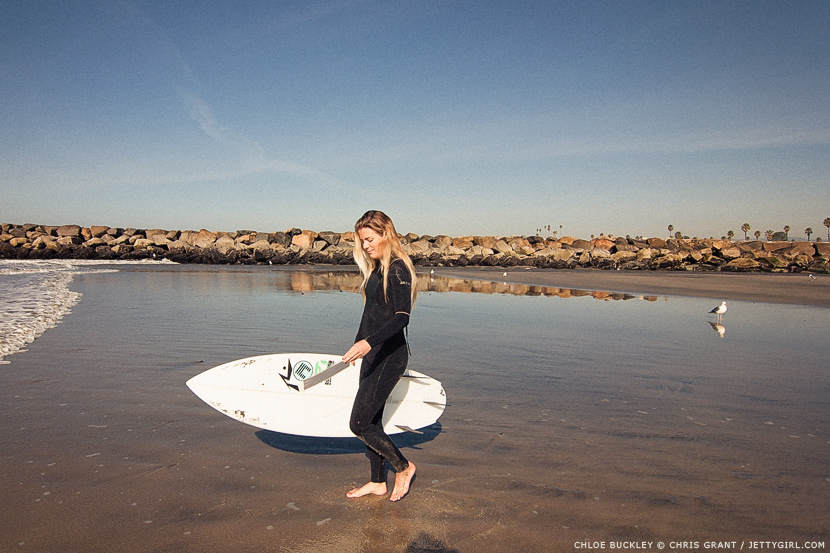 Surfer girl Chloe Buckley walks across the low tide sand in Oceanside, California. Surf photo by Chris Grant, Jettygirl Online Surf Magazine.