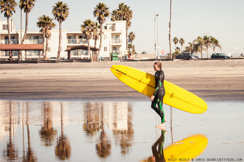 Kelly Nicely walking across wet sand in Oceanside. Photo by Chris Grant, JettyGirl Online Surf Magazine