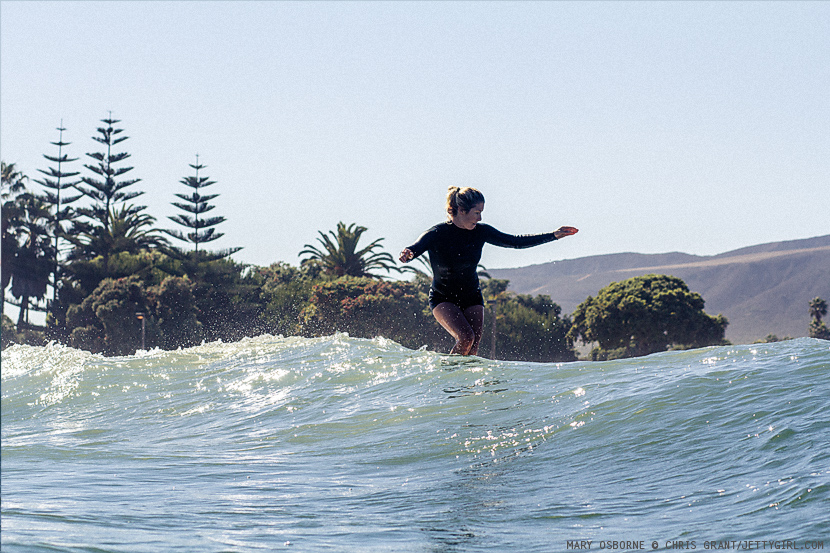 Mary Osborne cross-stepping on her new Cooperfish surfboard. Surf photo by Chris Grant, Jettygirl.com