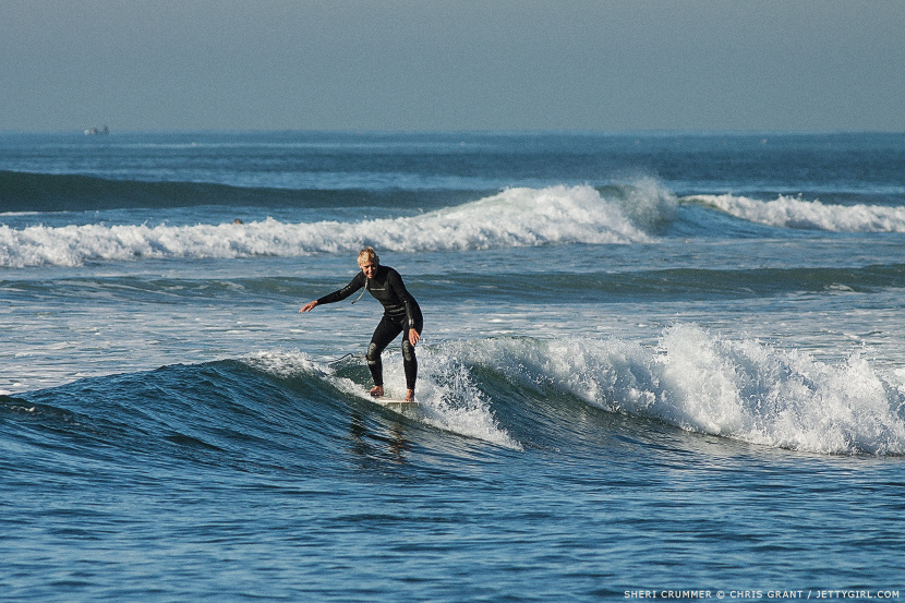 Sheri Crummer hangs five on a glassy inside right. Surf photo by Chris Grant, Jettygirl Online Surf Magazine.