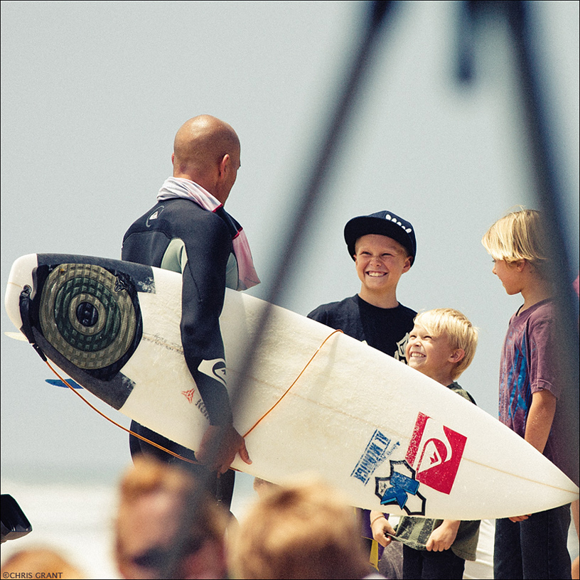 Kelly Slater spends a moment with three young surfers and leaves a positive impression that will last a lifetime. Chris Grant photo.