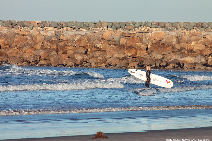 Tory Gilkerson enters the water for a surf session at Oceanside Harbor. Andrew Grant photo on Jettygirl Online Surf Magazine.