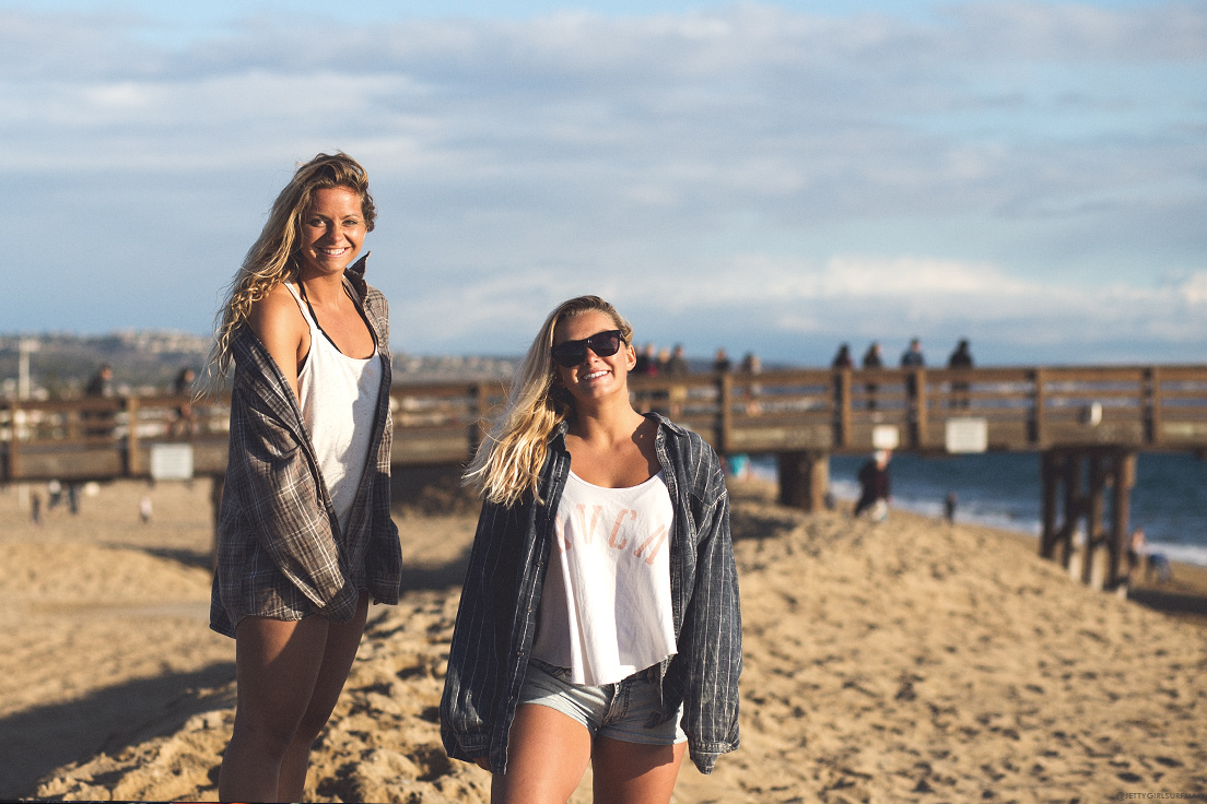 New Jersey surfers, Casey Kwiecinski and Kristen Acerra, share a smile at Balboa Pier. Visit Newport Beach - Enriching in Every Sense. Photo by Chris Grant, JettyGirl Surf Magazine
