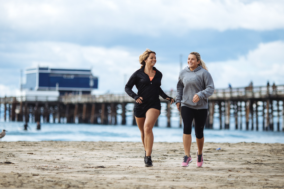 New Jersey surfers, Casey Kwiecinski and Kristen Acerra, take in an early morning run at Newport Pier. Visit Newport Beach - Enriching in Every Sense. Photo by Chris Grant, JettyGirl Surf Magazine