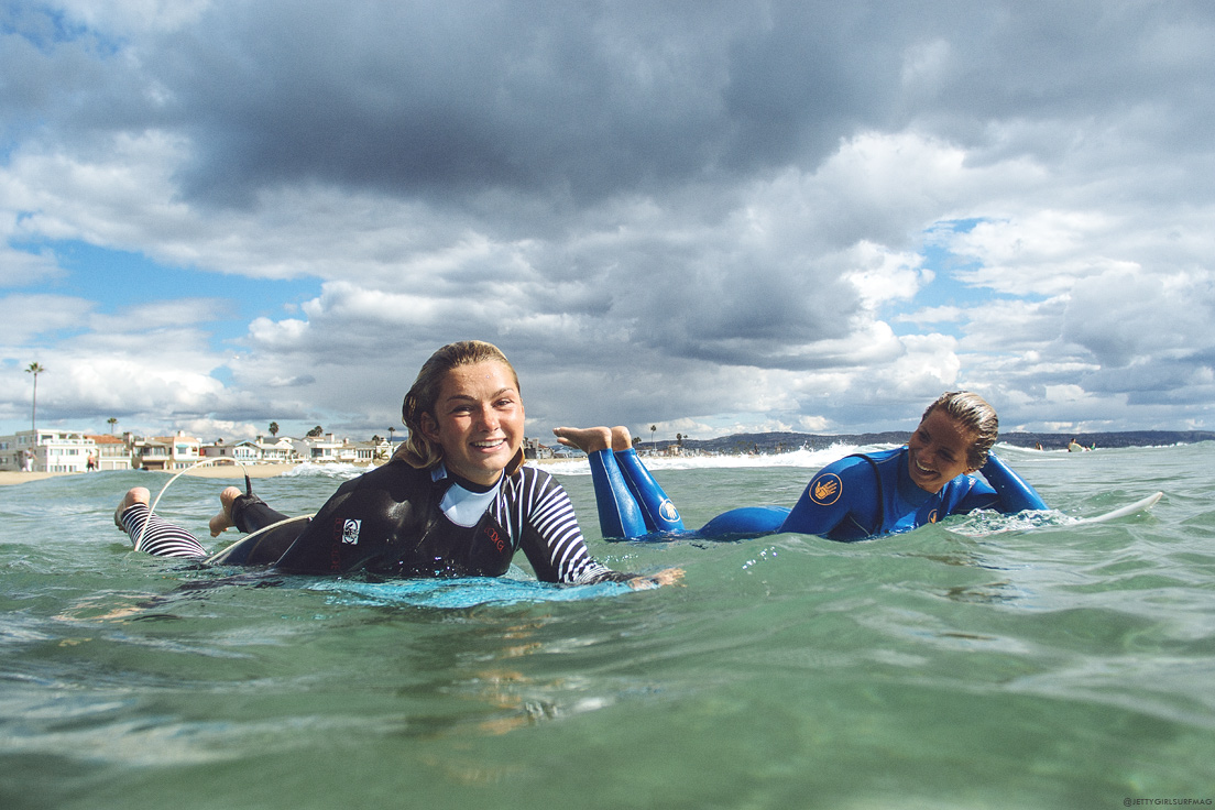 New Jersey female surfers, Kristen Acerra and Casey Kwiecinski, share a smile at Newport Pier. Visit Newport Beach - Enriching in Every Sense. Photo by Chris Grant, JettyGirl Surf Magazine