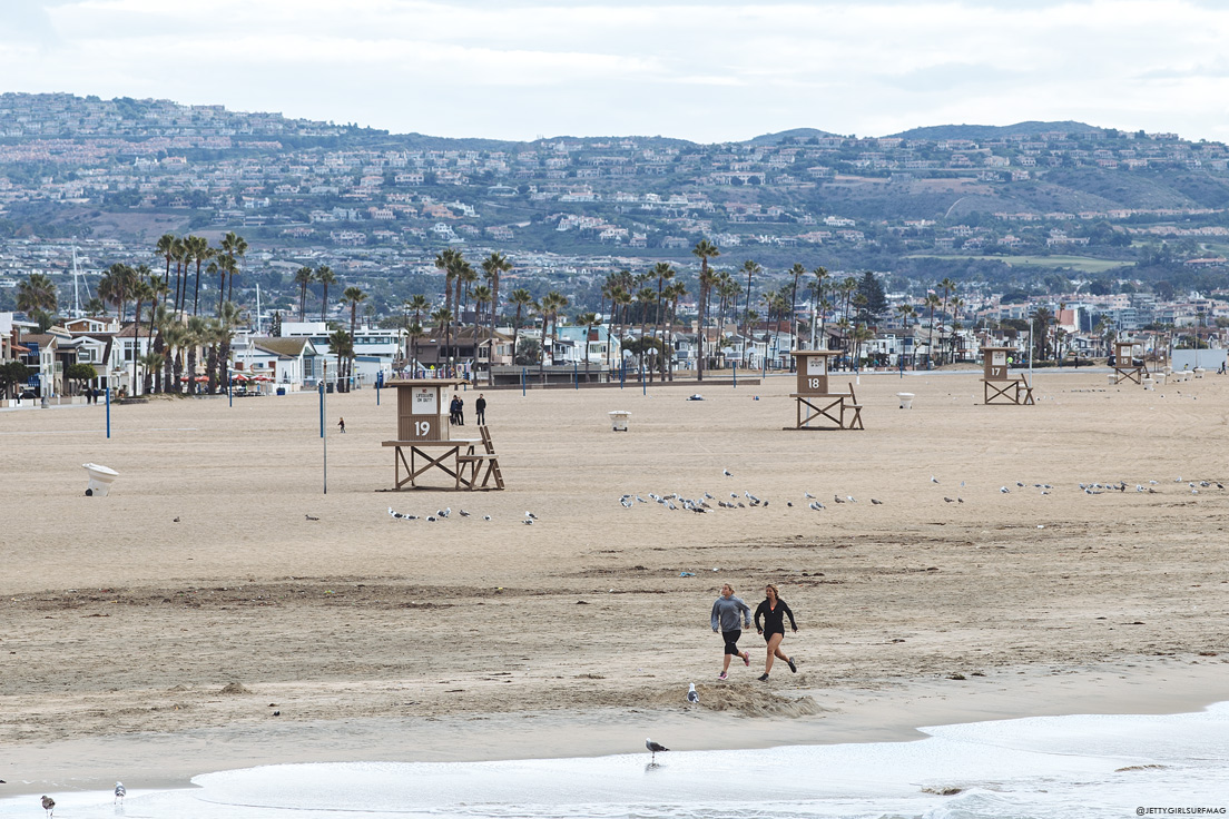 Two women run along the sand in Newport Beach. Visit Newport Beach - Enriching in Every Sense. Photo by Chris Grant, JettyGirl Surf Magazine