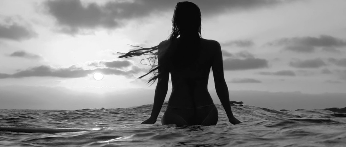 Surfer girl, Tia Blanco, sitting on her longboard and looking toward the sunset. Frame grab from Justin Jung's surf film, A Short Escape, playing on Jettygirl Surf Magazine