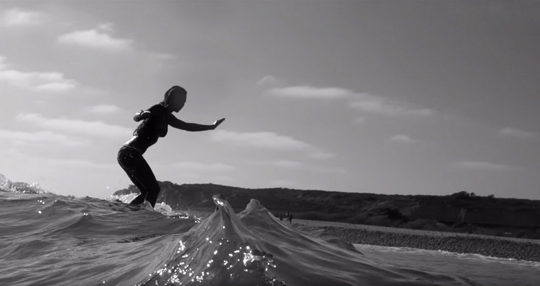 Surfer girl, Tia Blanco, cross-steps her longboard as she surfs on a clean, summer wave. Frame grab from Justin Jung's surf film,  A Short Escape, playing on Jettygirl Surf Magazine