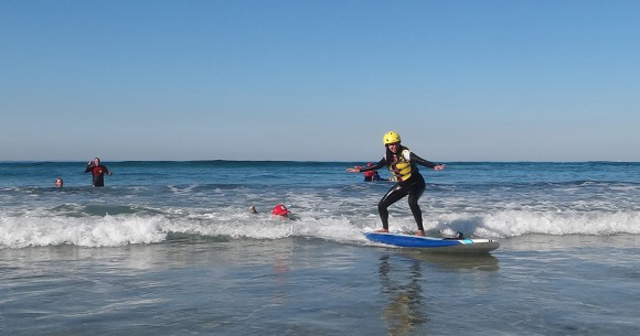 Haben Girma surfs a wave in San Diego with Surf Diva