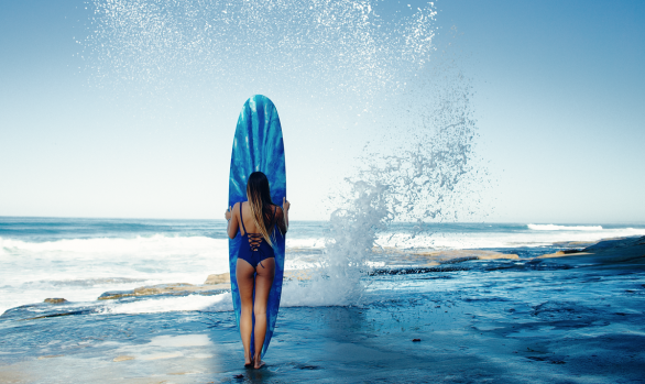 Izzy Poulin standing in front of surfboard with spray flying off the rocks, San Diego County - Chris Grant Photo for JettyGirl Surf Magazine