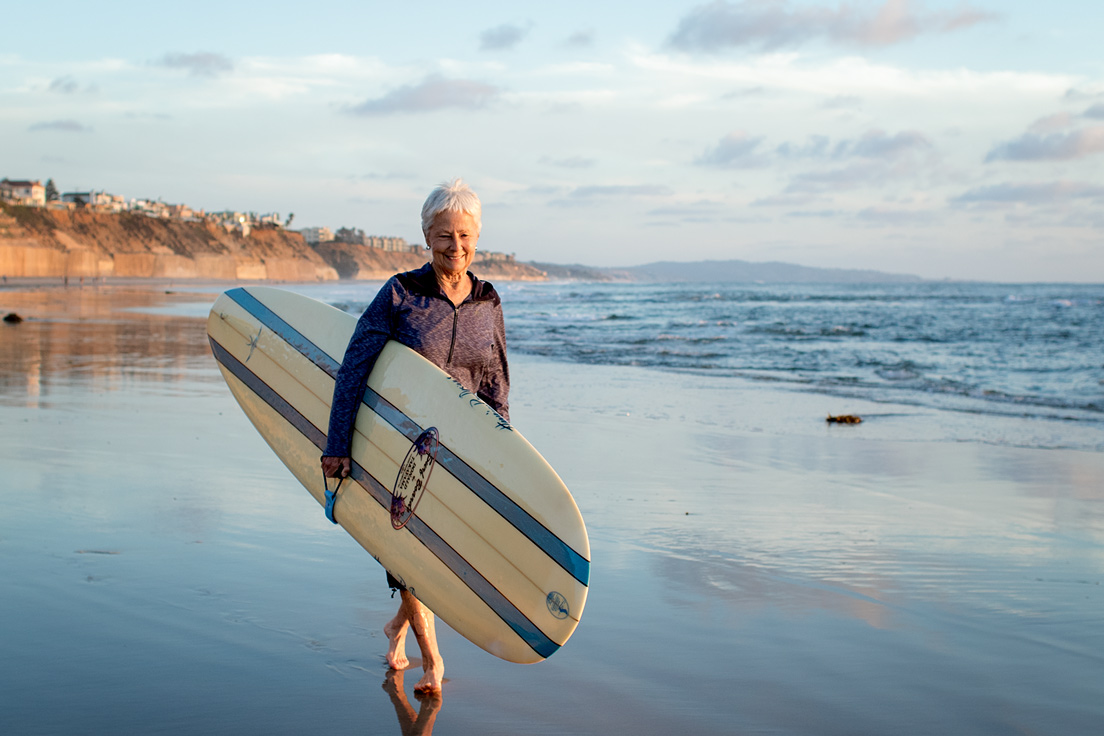 linda-benson-late-afternoon-beach-walk-with-donald-takayama-surfboard-jettygirl