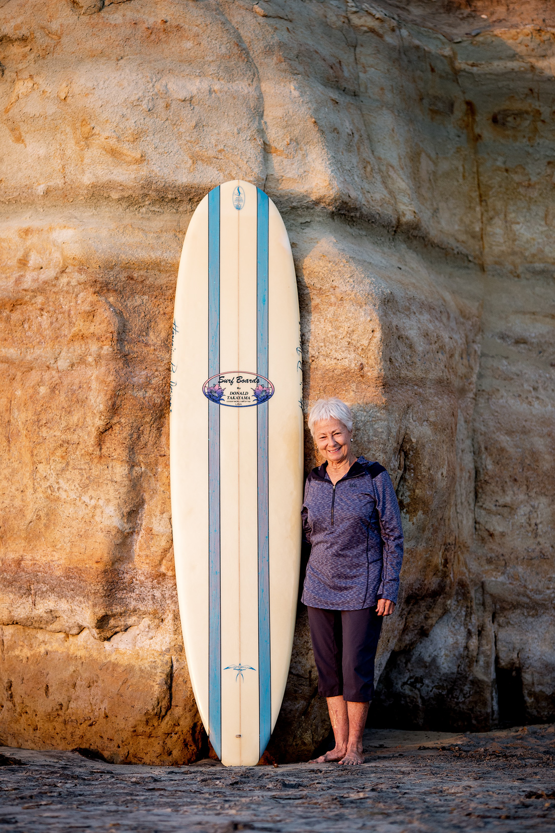 linda-benson-with-donald-takayama-surfboard-chris-grant-photo